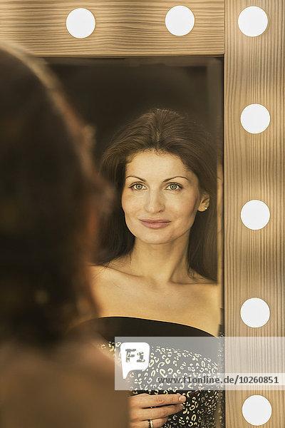Spiegelung der schönen Frau im Spiegel