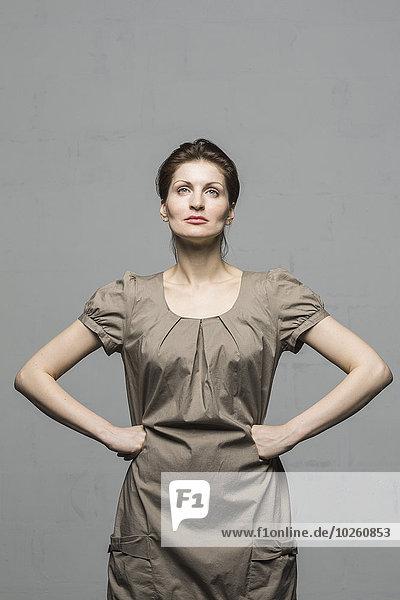 Selbstbewusstes Model mit Händen auf der Hüfte vor grauem Hintergrund stehend
