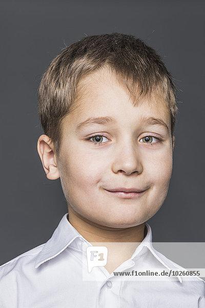 Porträt des lächelnden Jungen vor grauem Hintergrund