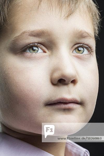 Nahaufnahme des nachdenklichen Jungen vor schwarzem Hintergrund
