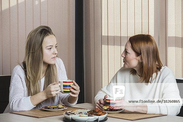 Mutter und Tochter unterhalten sich beim Frühstück zu Hause