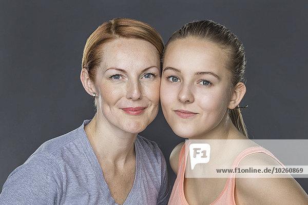 Porträt von lächelnder Mutter und Tochter vor grauem Hintergrund
