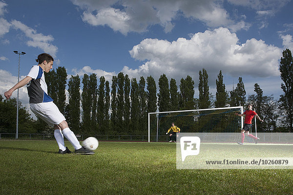 Volle Länge des jungen Fußballspielers  der den Ball in Richtung Torpfosten kickt.