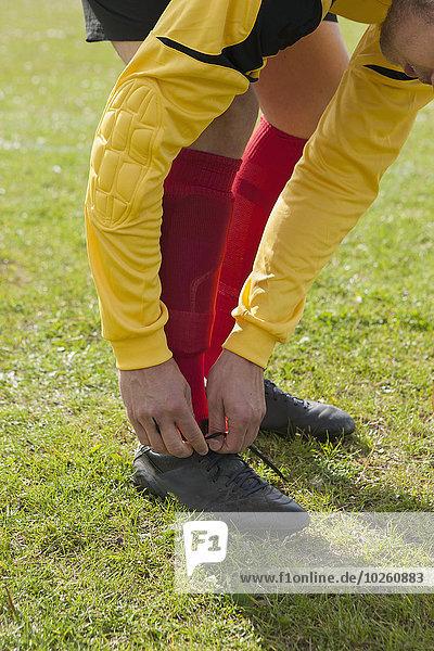 Niedriger Abschnitt des Mannes  der Fußballschuhe auf dem Spielfeld bindet.