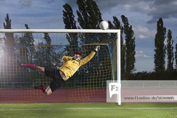 Volle Länge der Fußball-Torhüter Tauchen zu blockieren Ball
