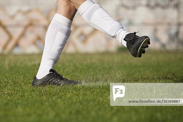 Niedriger Abschnitt des Fußballspielers  der auf dem Rasen kickt.