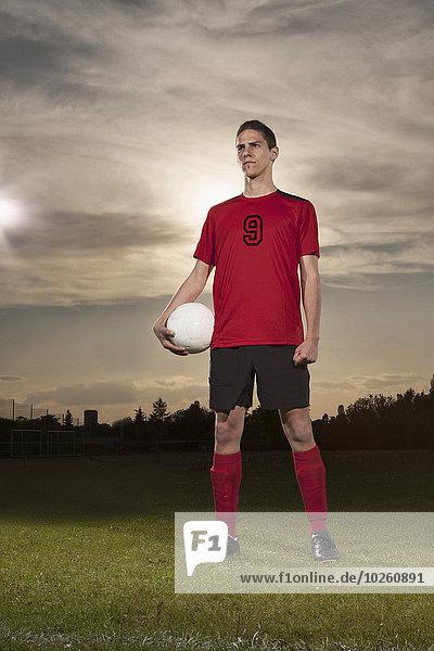 Volle Länge des bestimmten Fußballspielers  der den Ball auf dem Spielfeld hält.