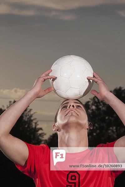 Junger Fußballspieler balanciert Ball auf Kopf