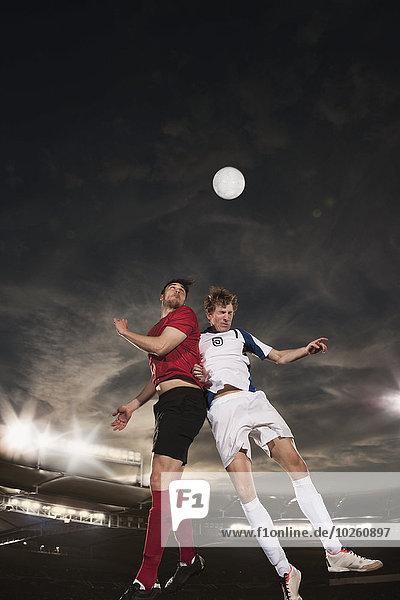 Männliche Fußballspieler  die den Ball während des Spiels steuern