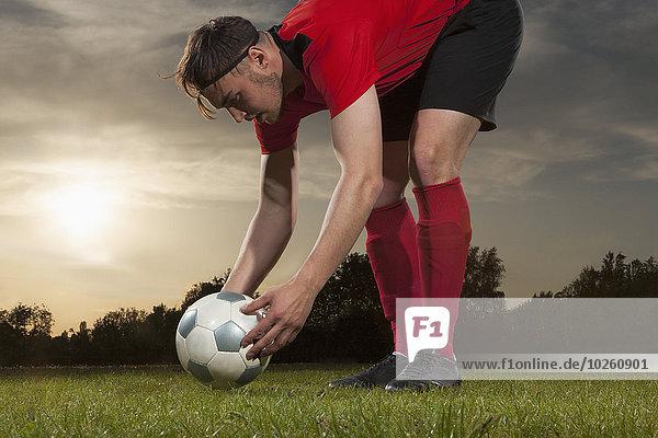 Volle Länge des jungen Fußballspielers  der den Ball auf dem Spielfeld positioniert.