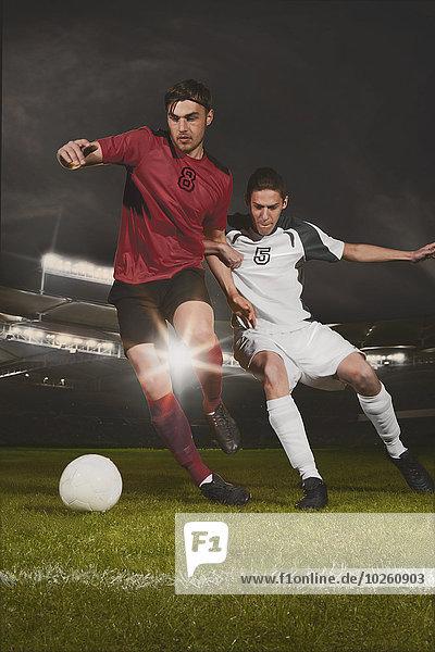 Volle Länge der jungen männlichen Fußballspieler  die den Ball während des Spiels in Angriff nehmen.