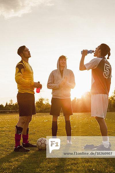 Volle Länge der jungen Fußballspieler  die auf dem Spielfeld stehen