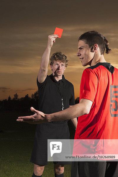 Schiedsrichter zeigt dem Fußballspieler rote Karte, Schiedsrichter zeigt dem Fußballspieler rote Karte