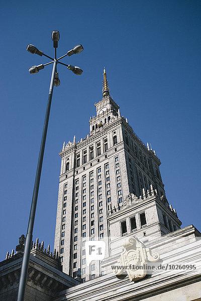 Palast der Kultur und Wissenschaft und Straßenbeleuchtung gegen klaren blauen Himmel