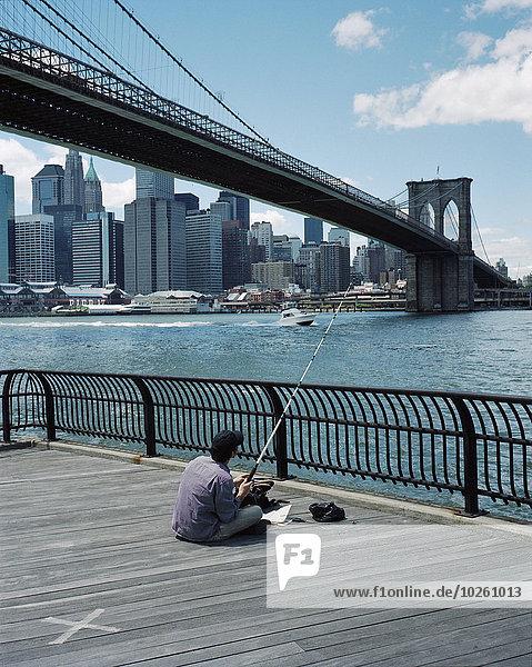 Rückansicht des sitzenden Mannes mit Brooklyn Bridge und Wolkenkratzern im Hintergrund
