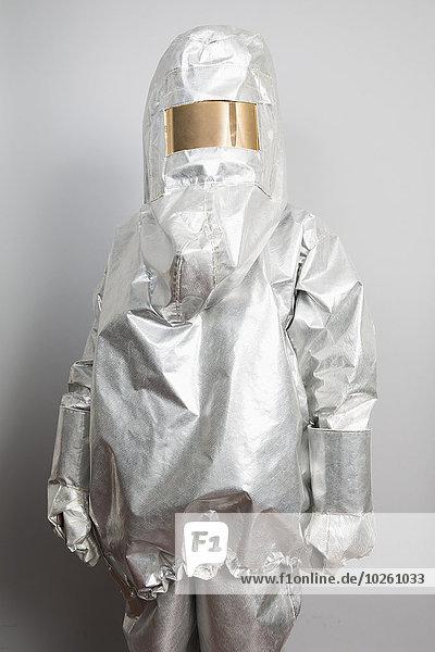 Eine Person in einem radioaktiven Schutzanzug  die vor einem grauen Hintergrund steht.