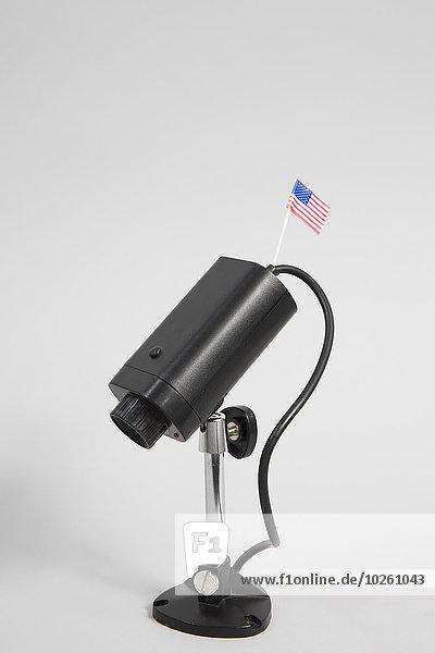 Nahaufnahme einer Sicherheitskamera mit amerikanischer Flagge vor weißem Hintergrund