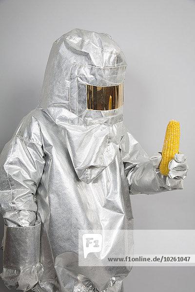 Eine Person in einem Strahlenschutzanzug  die einen Maiskolben hält.