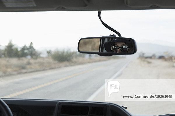 Spiegelung der Frau im Rückspiegel des Autos auf der Landstraße