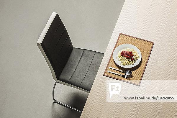 Spaghetti mit frischer Tomatensauce im Teller auf dem Tisch serviert