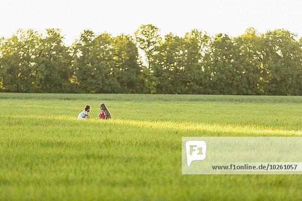 Fernbild von Mädchen  die auf einem grasbewachsenen Feld sitzen.