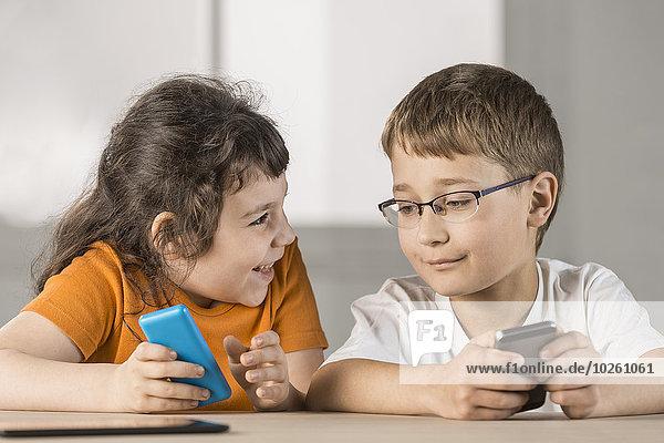 Geschwister mit dem Handy zu Hause