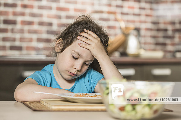 Trauriges Mädchen mit Kopf in der Hand beim Frühstück am Tisch