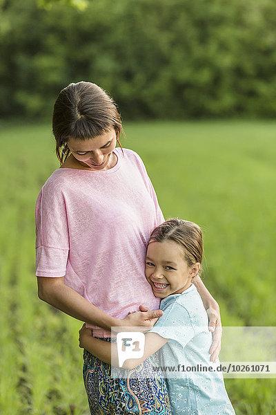 Lächelndes Mädchen umarmt Mutter auf dem Feld