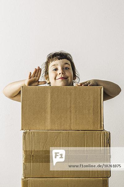 Porträt eines fröhlichen Mädchens,  das hinter gestapelten Kisten steht