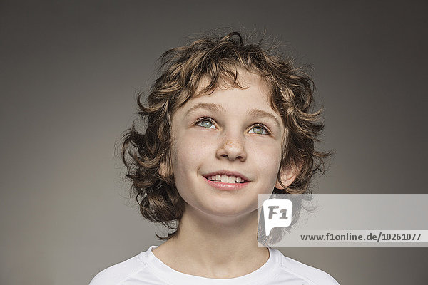 Nahaufnahme des nachdenklichen Jungen über grauem Hintergrund