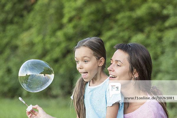 Mutter und Tochter spielen mit Seifenblase im Freien