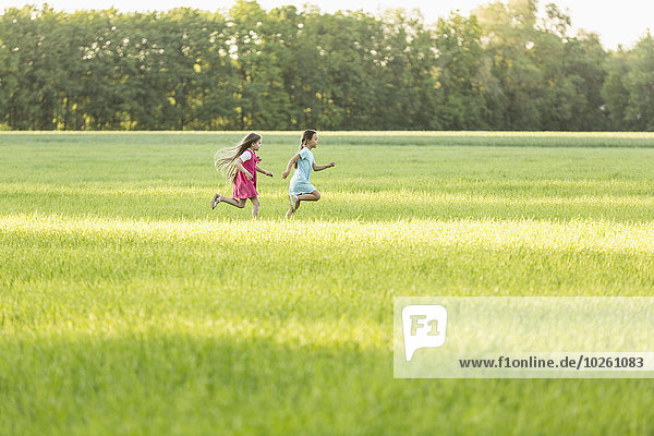 Seitenansicht von Mädchen  die auf einem Grasfeld laufen