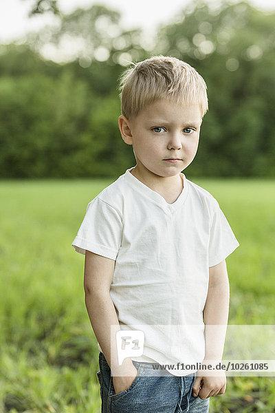Porträt des süßen Jungen stehend mit der Hand in der Tasche auf dem Feld