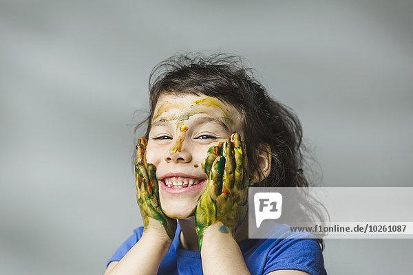 Lächelndes Mädchen mit gemaltem Gesicht und Händen über grauem Hintergrund