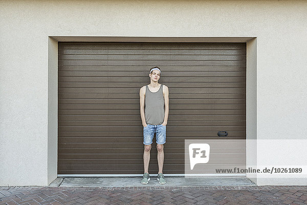 Ganzaufnahme eines jungen Mannes vor dem Garagentor