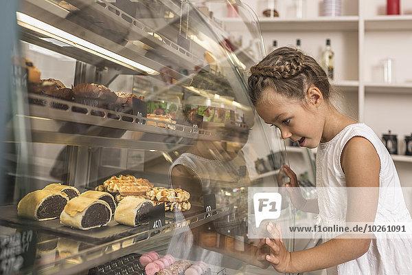 Seitenansicht des Mädchens  das das Dessert in der Bäckerei bewundert.
