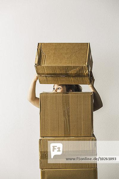 Mädchen schaut weg und stapelt Boxen vor weißem Hintergrund