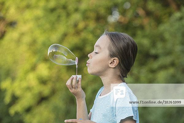 Seitenansicht des Mädchens beim Blasen im Freien
