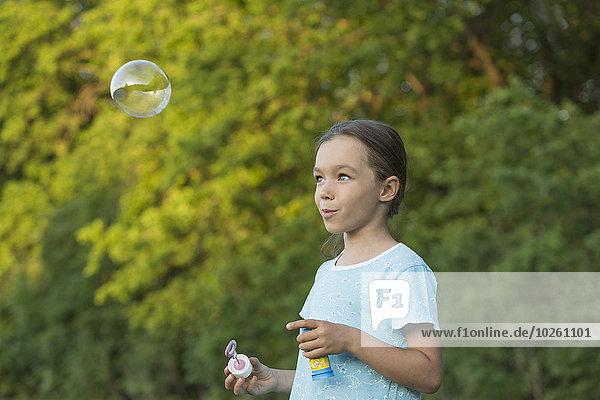 Fröhliches Mädchen bläst Blase im Freien