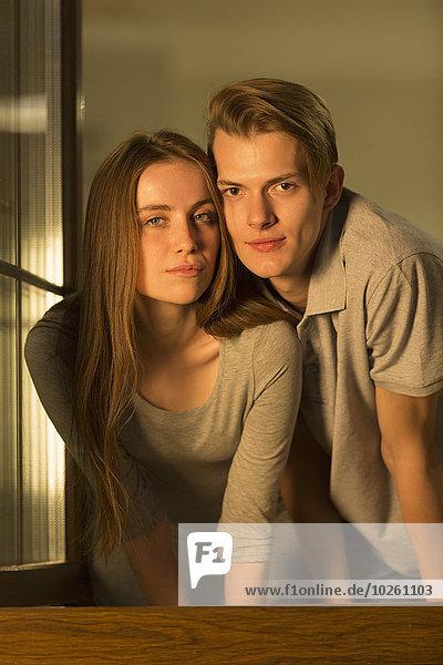 Porträt eines glücklichen jungen Paares am Fenster