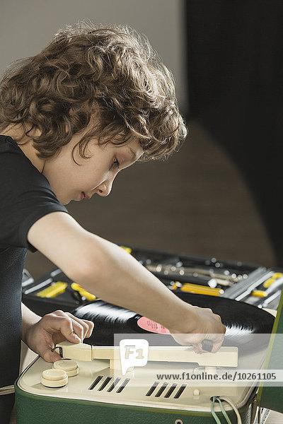 Junge spielt zu Hause Schallplatte