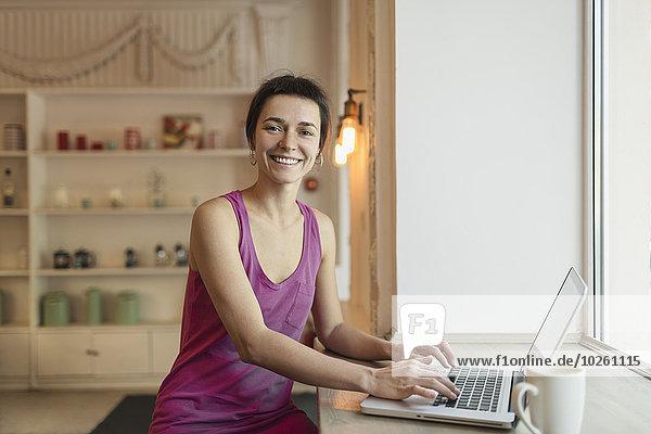 Porträt einer lächelnden mittleren erwachsenen Frau mit Laptop im Cafe