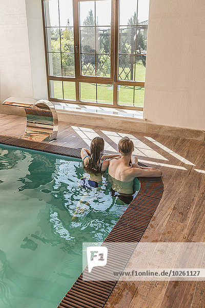 Rückansicht des jungen Paares am Rande des Swimmingpools