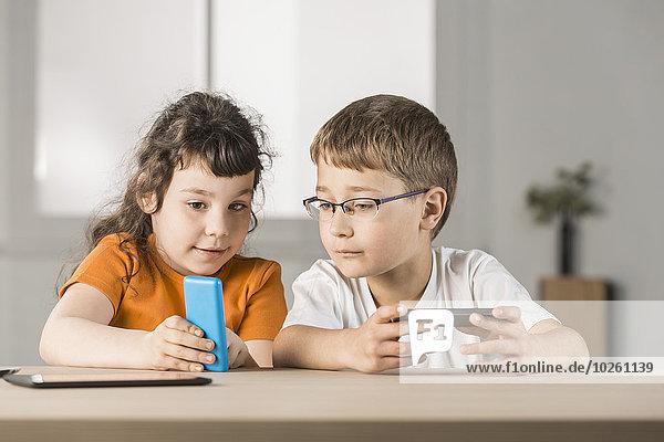 Schwester zeigt dem Bruder etwas auf dem Handy zu Hause