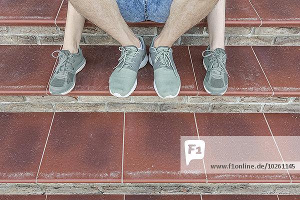 Niedriger Teil des jungen Paares auf der Treppe sitzend