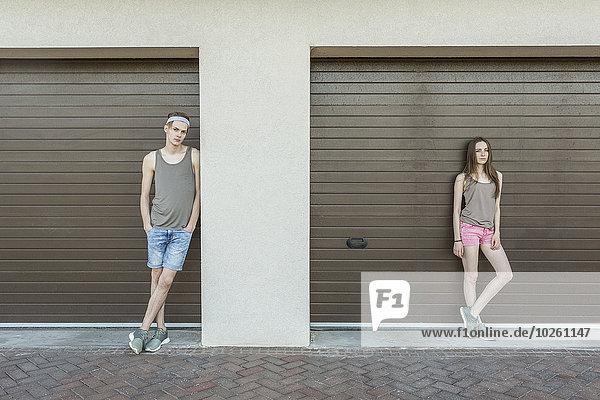 Junger Mann und Frau  die sich gegen eine geschlossene Garage lehnen.