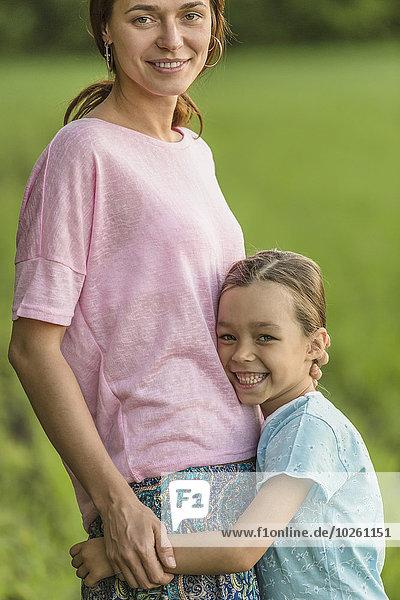 Porträt eines lächelnden Mädchens  das die Mutter auf dem Feld umarmt.