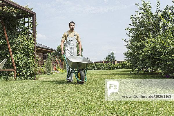 Junger Mann mit Schubkarre im Hinterhof