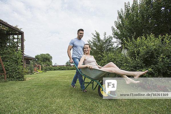 Mann schiebt Freundin in Schubkarre im Hinterhof