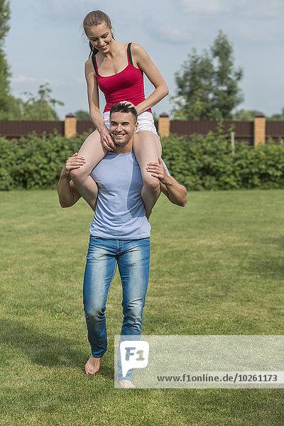 Volle Länge des glücklichen jungen Mannes  der die Frau auf den Schultern im Hinterhof trägt.